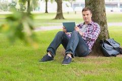 Estudante feliz que usa seu PC da tabuleta fora da inclinação na árvore Imagem de Stock