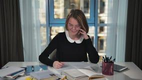 A estudante feliz toma chamar um smartphone Faz os trabalhos de casa Sorri video estoque