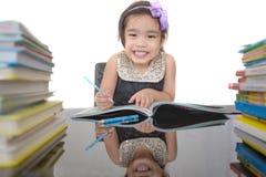 A estudante feliz trabalha em seus trabalhos de casa, escreve algo em seu bloco de notas fotografia de stock