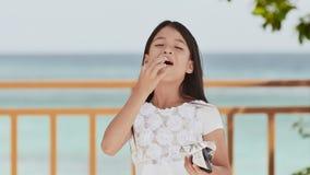A estudante filipino no vestido branco sorri, comendo microplaquetas de batata friáveis Paisagem tropical As palmas verão vídeos de arquivo