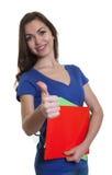 Estudante fêmea de riso com cabelo escuro longo e documento que mostram o polegar Imagens de Stock Royalty Free