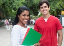 Estudante fêmea latin de riso com o amigo caucasiano exterior Fotos de Stock Royalty Free