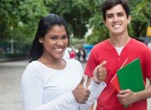 Estudante fêmea latin de riso que mostra o polegar com amigo caucasiano Imagens de Stock Royalty Free