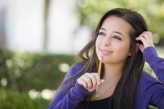 Estudante fêmea pensativo de raça misturada com o lápis no terreno Fotografia de Stock