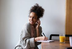 Estudante fêmea que trabalha em casa e que fala no telefone celular Imagem de Stock