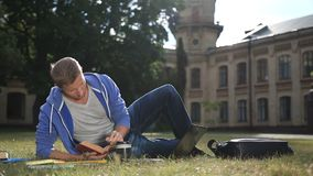 Estudante focalizado considerável que estuda no gramado do terreno vídeos de arquivo