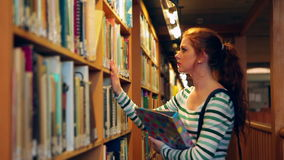Estudante focalizado que selecciona um livro na biblioteca filme