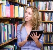 Estudante focalizado que usa um tablet pc em uma biblioteca Fotos de Stock