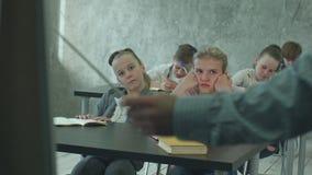 A estudante infeliz na classe escuta um professor vídeos de arquivo
