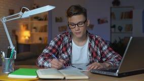 Estudante inteligente nos vidros que terminam os trabalhos de casa que mostram os polegares-acima à câmera vídeos de arquivo