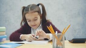 Estudante inteligente que senta-se na tabela Durante isto, escreve uns trabalhos de casa, contando em uma calculadora vídeos de arquivo