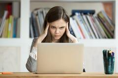 Estudante interessada focalizada que aprende o exame difícil com lapt imagens de stock
