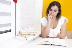 A estudante lê o livro e prepara-se para exames na universidade foto de stock royalty free