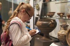 Estudante Looking At Artifacts caso que na viagem ao museu fotos de stock