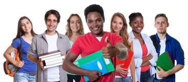 Estudante masculino afro-americano que mostra o polegar com grupo de estudantes Foto de Stock Royalty Free