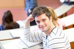 Estudante masculino deleitado que sorri durante uma lição fotos de stock