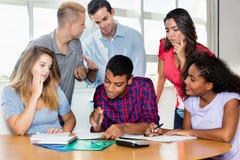 Estudante masculino indiano com grupo de estudantes internacionais um teac imagem de stock