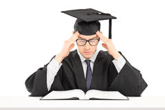 Estudante masculino no vestido da graduação que tenta concentrar-se no studyin fotos de stock royalty free
