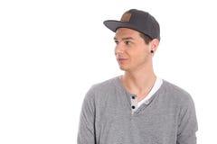 Estudante masculino novo com o tampão que olha isolado lateralmente em b branco fotografia de stock royalty free