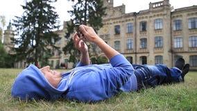 Estudante masculino novo que consulta no telefone esperto filme