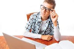 Estudante masculino novo que faz lições com o portátil e os livros que sentam-se na tabela no estúdio no fundo branco imagem de stock royalty free