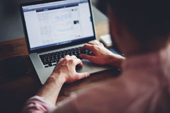 Estudante masculino novo que texting no computador que senta-se na tabela de madeira