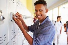 Estudante masculino Opening Locker da High School foto de stock royalty free