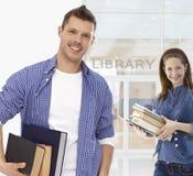 Estudante masculino que guarda livros na biblioteca Imagem de Stock