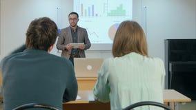 Estudante masculino que levanta a mão e que faz a professor uma pergunta que senta-se na tabela vídeos de arquivo