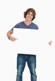 Estudante masculino que prende e que aponta uma placa branca foto de stock