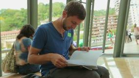 Estudante masculino que prepara-se para o teste, sentando-se no salão da universidade e lendo notas video estoque