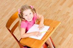 Estudante: Menina de sorriso que senta-se na mesa da escola com Copyspace foto de stock