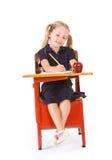 Estudante: Menina na farda da escola que faz trabalhos de casa na mesa fotos de stock royalty free