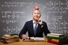 Estudante miling de pensamento com a maçã na cabeça que prepara-se para testar Foto de Stock Royalty Free