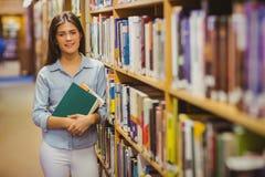 Estudante moreno de sorriso que está ao lado das estantes quando guardar registrar foto de stock