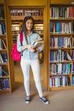 Estudante moreno de sorriso que está ao lado das estantes quando guardar registrar fotos de stock