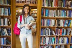 Estudante moreno de sorriso que está ao lado das estantes quando guardar registrar fotos de stock royalty free