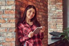 A estudante moreno de sorriso vestiu-se em uma camisa e nas calças de brim de manta que guardam a tabuleta digital ao inclinar-se fotografia de stock royalty free
