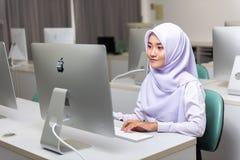 Estudante muçulmano que trabalha com o computador de Apple iMac imagens de stock
