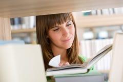 Estudante na biblioteca - a mulher feliz leu o livro Imagem de Stock