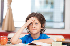Estudante na escola primária que pensa sobre a resolução de problemas Fotografia de Stock