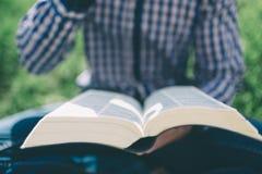 Estudante na rua a preparar-se para os exames O indivíduo está lendo um livro na rua Um homem farpado que descansa no Foto de Stock