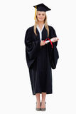 Estudante na terra arrendada graduada da veste seu diploma fotografia de stock royalty free