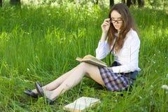 A estudante no parque leu o livro Fotos de Stock Royalty Free
