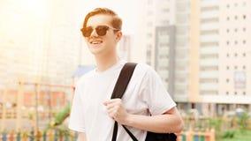 Estudante nos óculos de sol com sorrisos da trouxa Exterior, luz solar imagens de stock royalty free