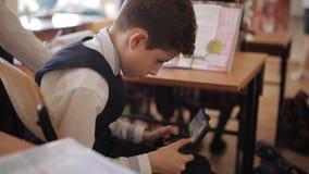 Estudante nos jogos da classe com um controlador sob a mesa O estudante joga com seu telefone sob a mesa no vídeos de arquivo