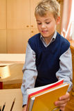 A estudante nova embala livros atrás de uma mesa da escola imagens de stock