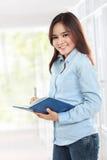 Estudante novo bonito que guarda o livro e a escrita Foto de Stock Royalty Free