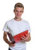 Estudante novo com cabelo louro que lê o seu registros fotos de stock