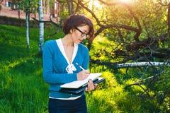 Estudante novo com caderno Em linha estudando fora o conceito Imagens de Stock